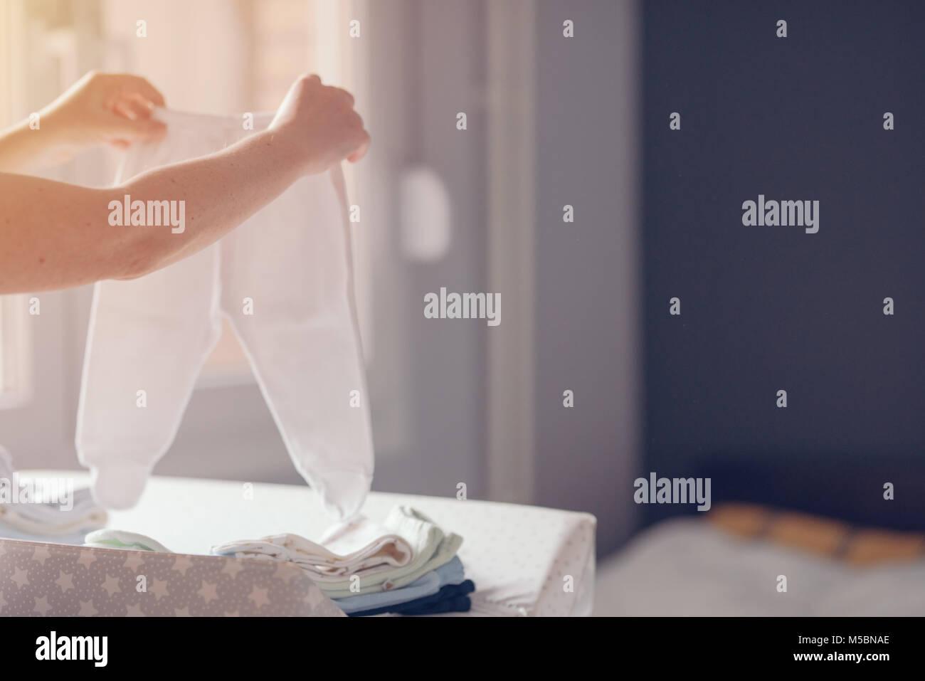 Tri des vêtements de bébé nouveau-né de la mère pour le repassage à domicile dans Photo Stock