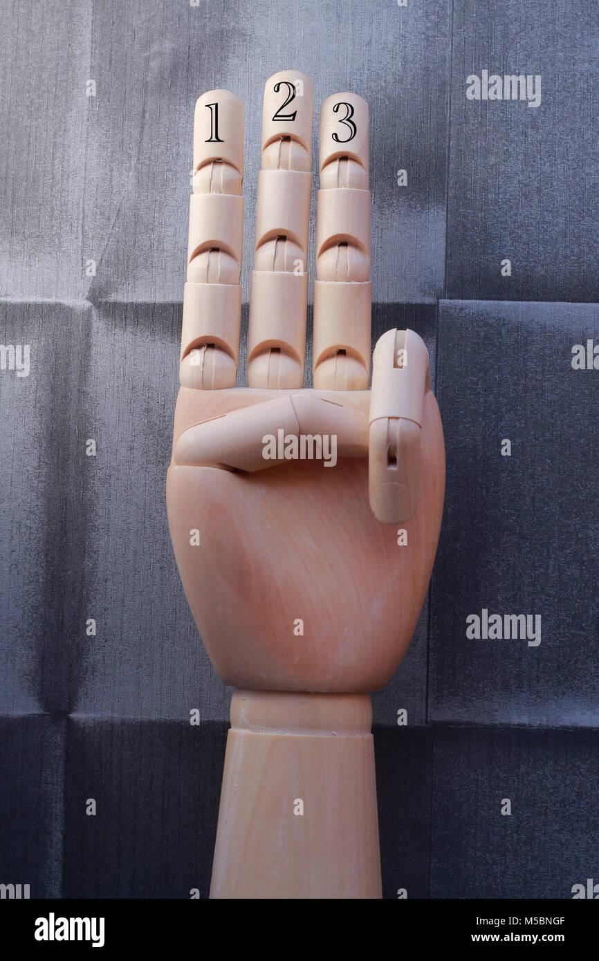 Main en bois avec trois doigts soulevées et numérotés avec des chiffres 1, 2 et 3, sur un fond papier Photo Stock