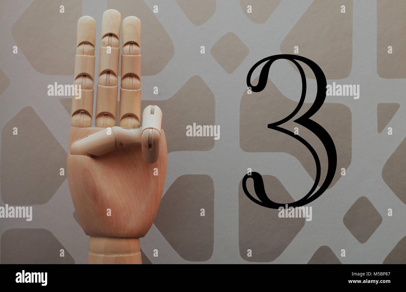 Main en bois articulé avec trois doigts a grandi à allusion à numéro trois, sur fond de papier Photo Stock