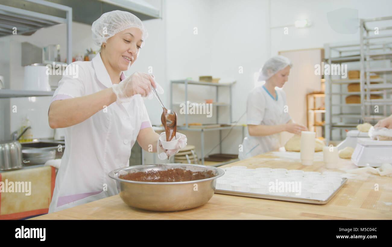 Baker se mélange crème au chocolat dans un bol en métal et faire des gâteaux Photo Stock