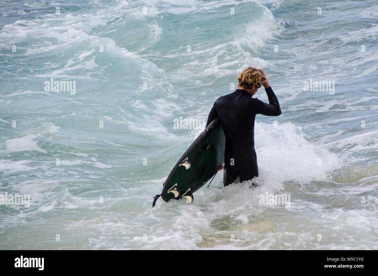 Balades à travers les vagues de surf masculin avec surf. La liberté et l'attente comme un mâle quitte à Surfer la Banque D'Images