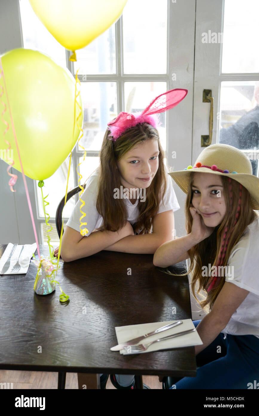 Deux jeunes enfants sont assis à une table en train de manger les aliments frits parti et de boire des milkshakes Photo Stock