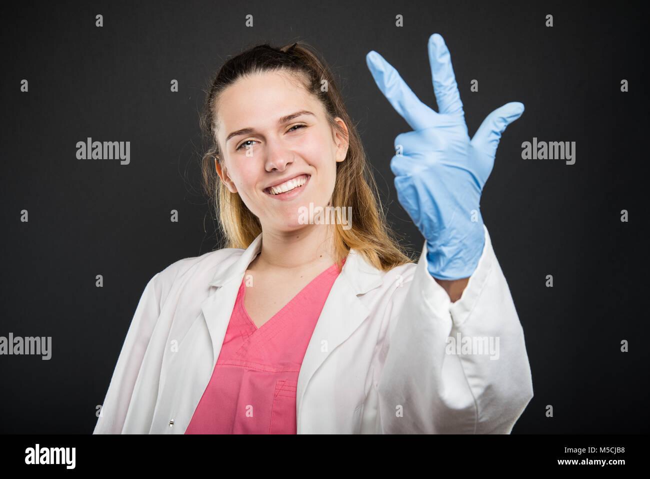Jeune médecin portrait portant robe montrant le numéro trois sur fond noir Photo Stock