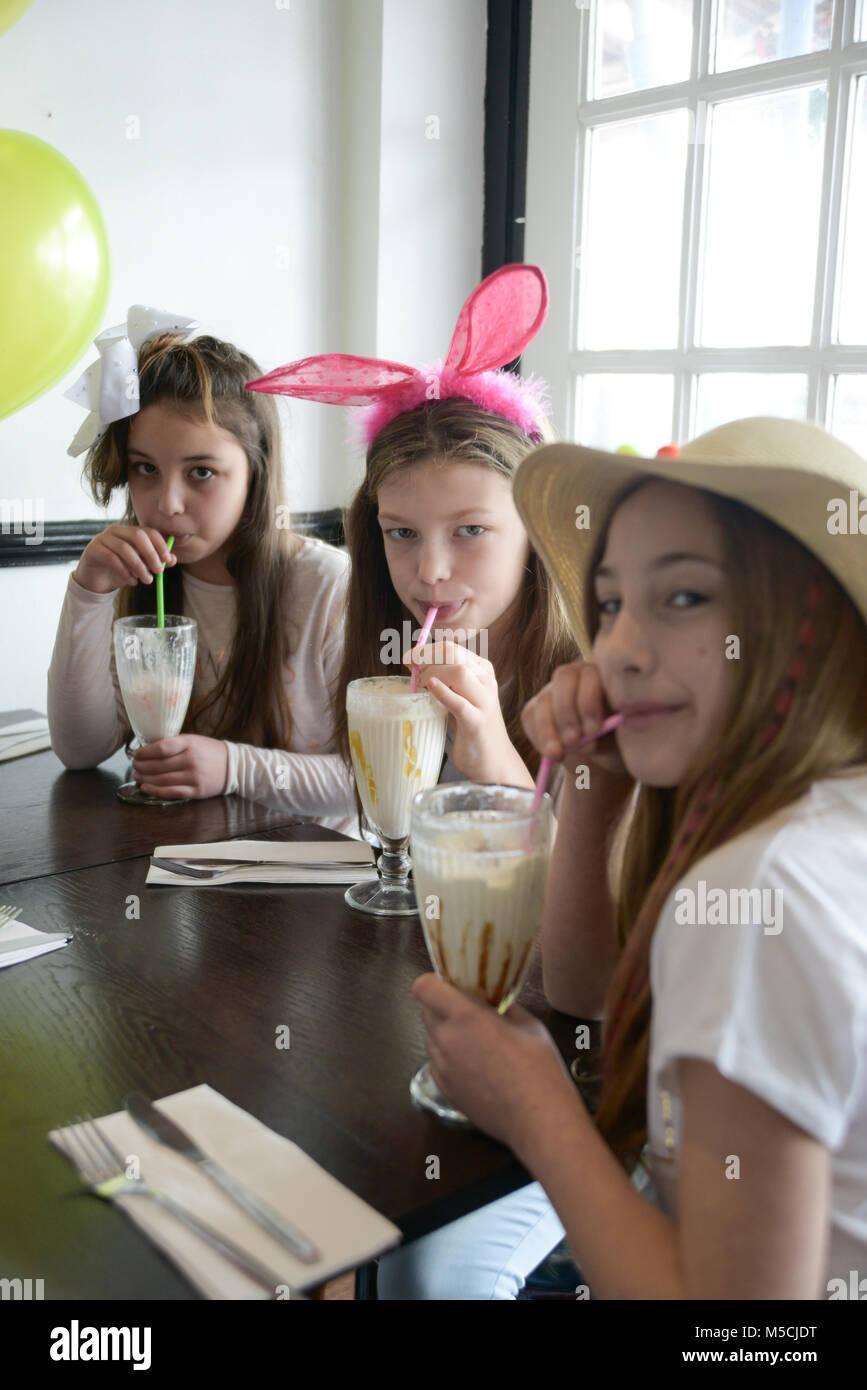 Trois jeunes enfants sont assis à une table en train de manger les aliments frits parti et de boire des milkshakes Photo Stock