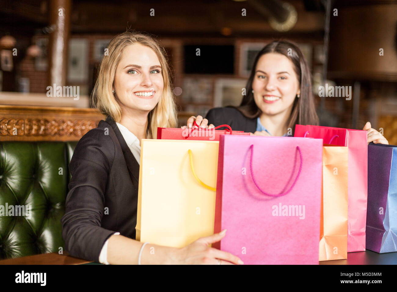 Young smiling blonde et brunette au contexte watch at camera sitting in a cafe après le magasinage Photo Stock