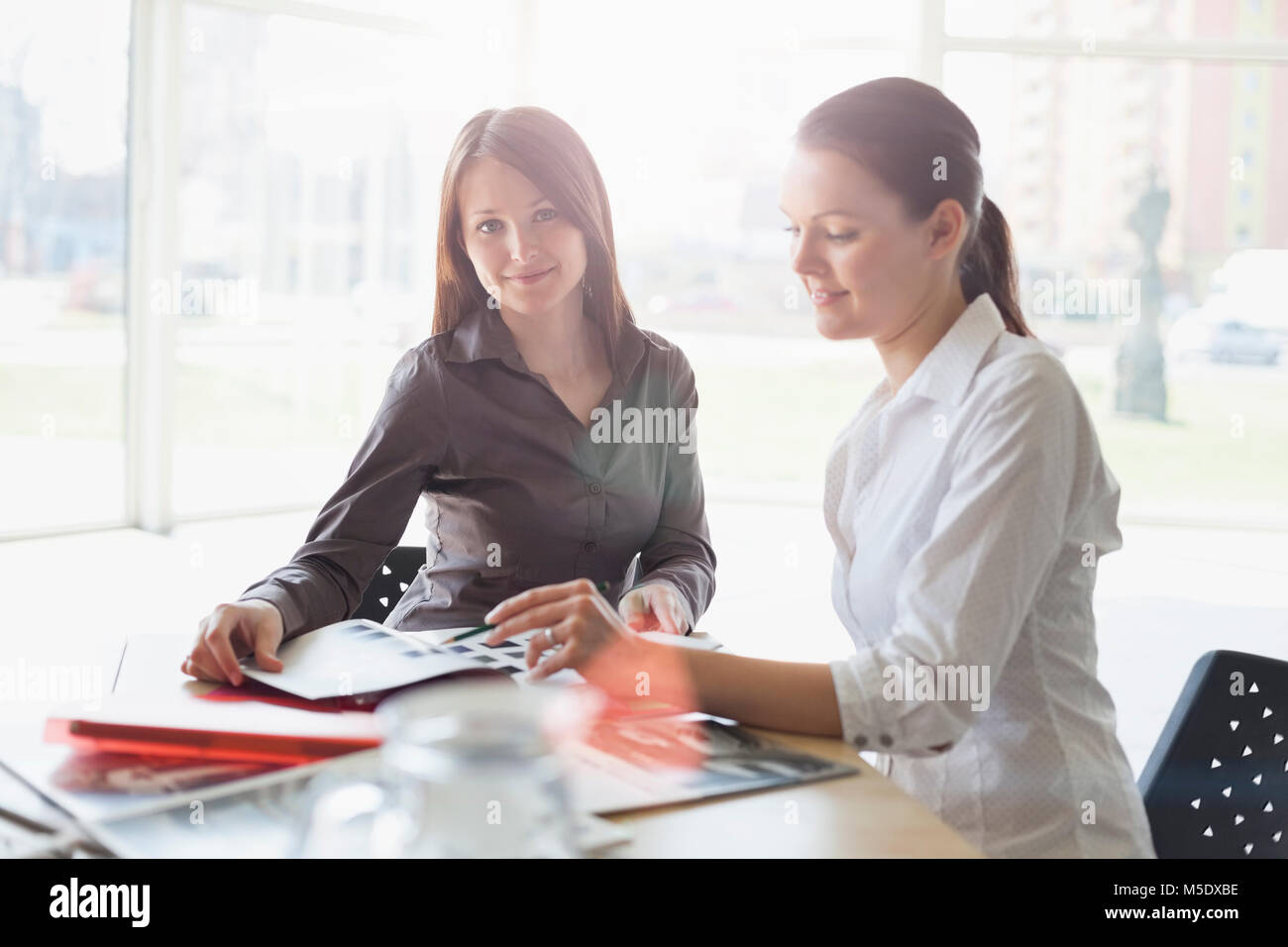 Portrait of young businesswoman with female colleague discuter at desk in office Banque D'Images