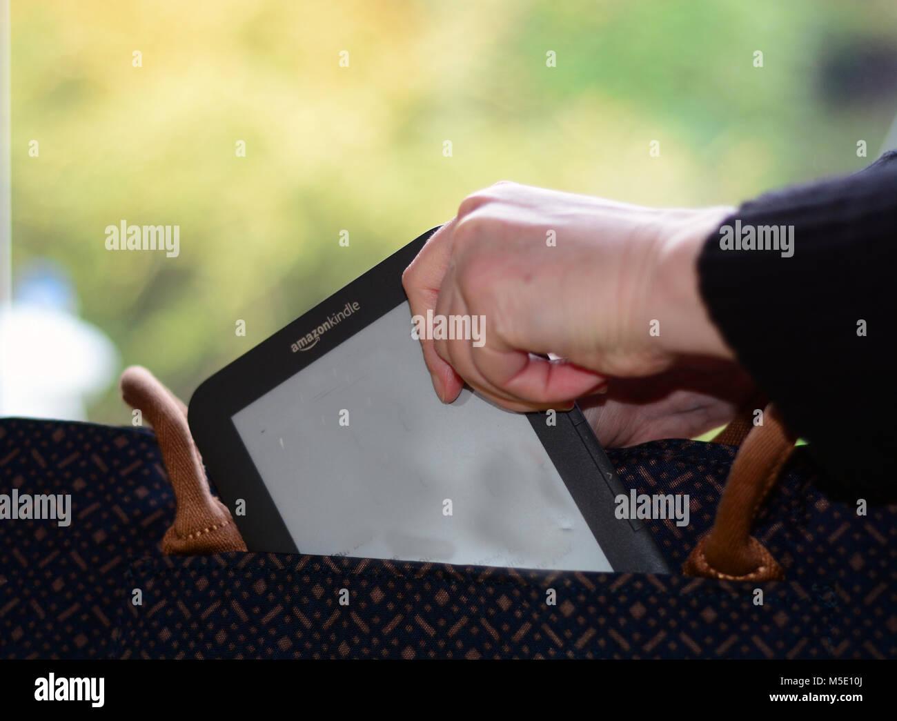 Woman putting un e-reader Kindle dans son sac à main (emballage pour maison de vacances/trajet du matin concept) Photo Stock