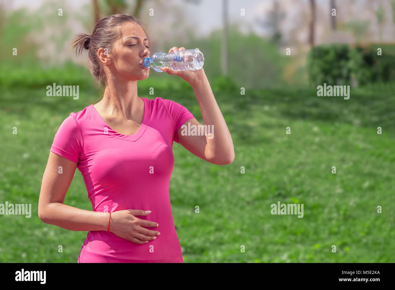 Runner Fitness Femme de l'eau potable dans le parc. Fille de l'athlète en faisant une pause pendant l'exécution d'hydrater pendant les chaudes journées d'été. Mode de vie sain et actif. Banque D'Images
