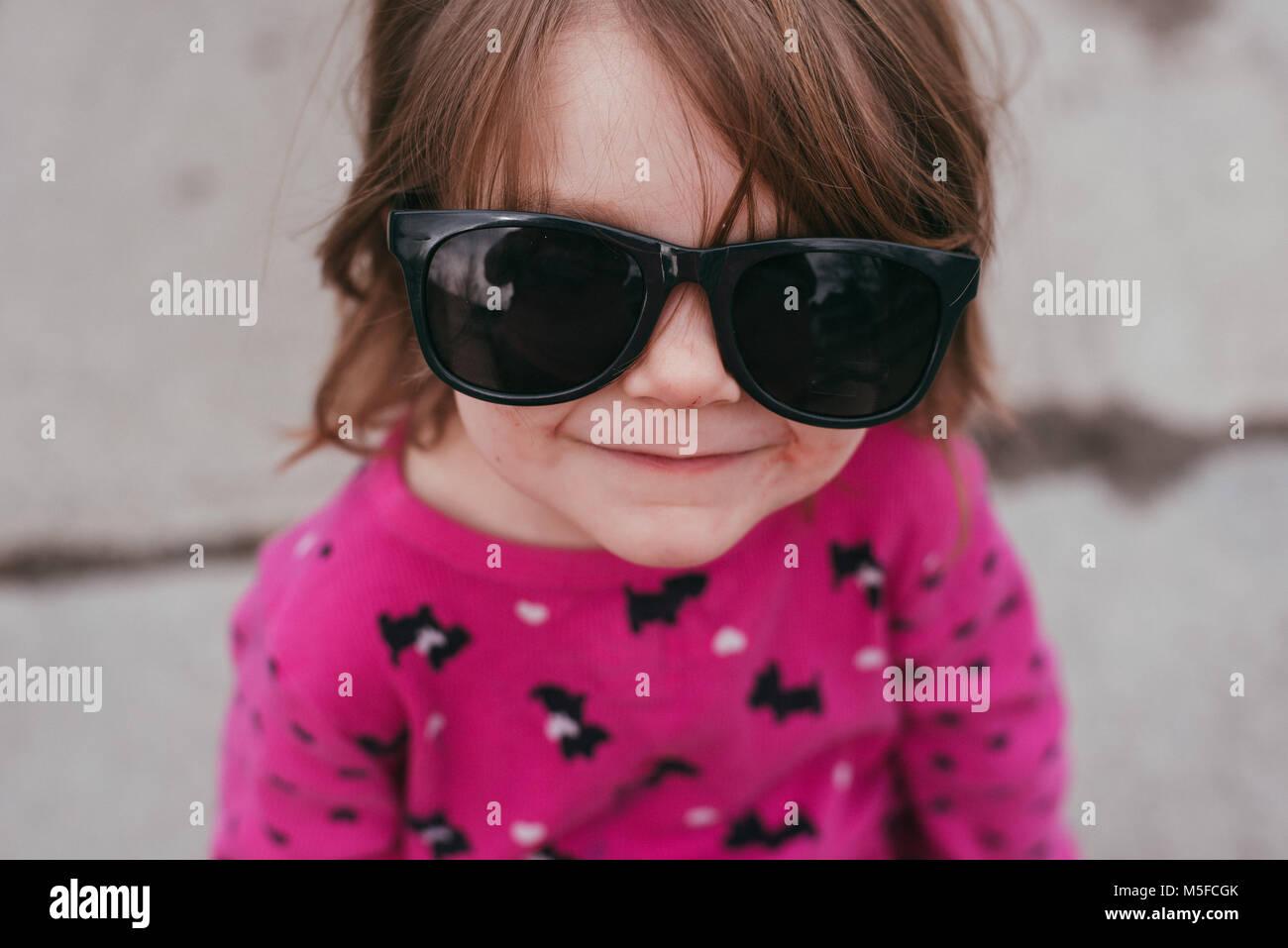 Un bébé fille portant un chandail rose et lunettes, debout sur un trottoir sur une journée chaude Photo Stock