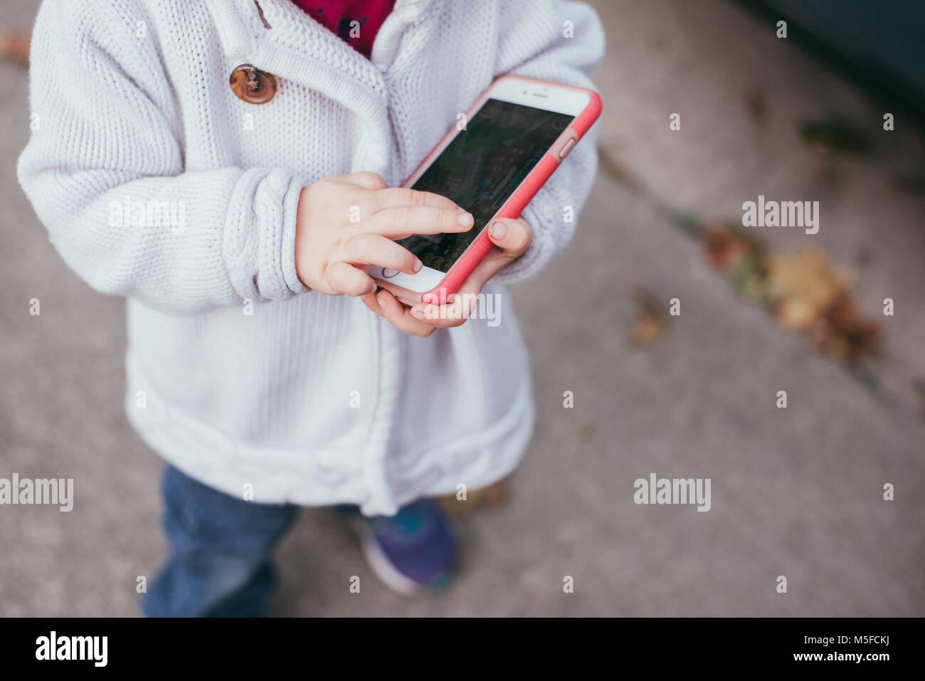 Un bambin filles joue sur un smartphone. Photo Stock