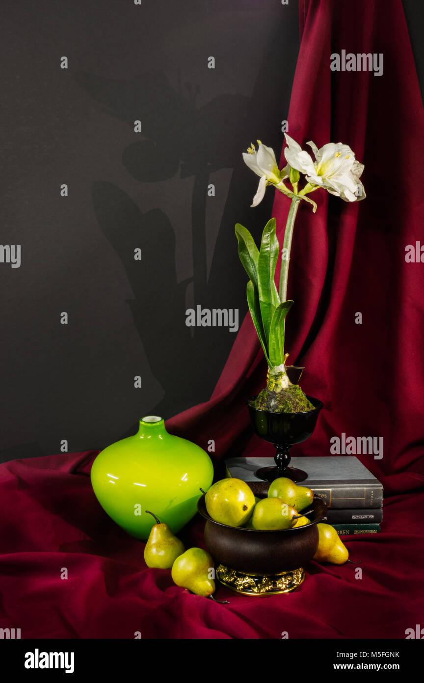 Encore une vie de poires, une fleur, un vase et composée de livres verts et jaunes contraste sur un fond drapé rouge. Banque D'Images