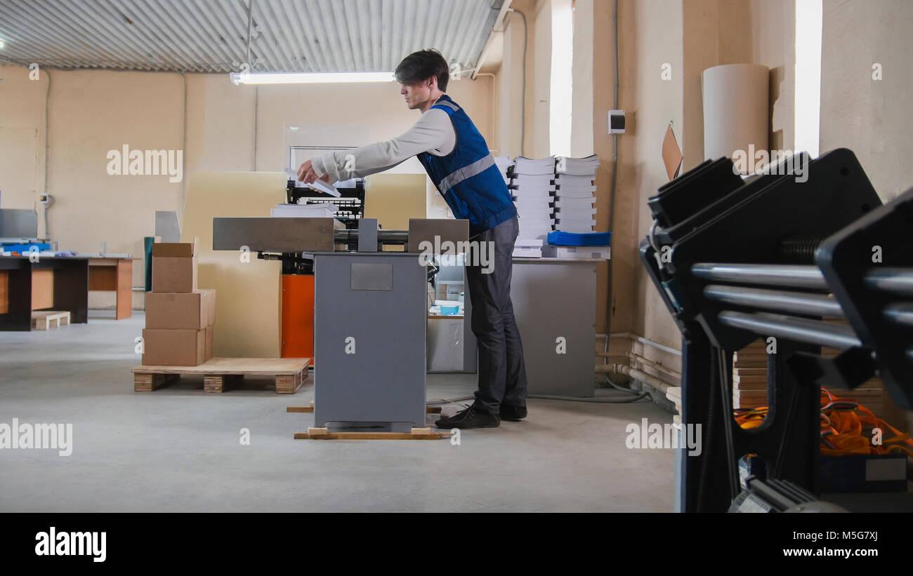 Travailleur et machine d'impression, de l'industrie polygraphique Photo Stock