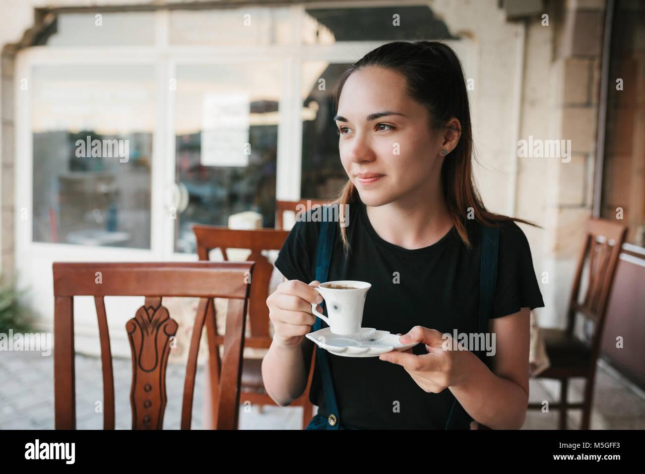 Belle femme de boire du café au café Photo Stock