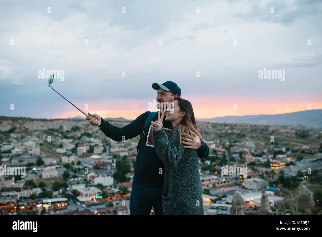 Un beau couple au coucher du soleil selfies sur fond de la ville de Göreme, en Cappadoce en Turquie. Photo Stock