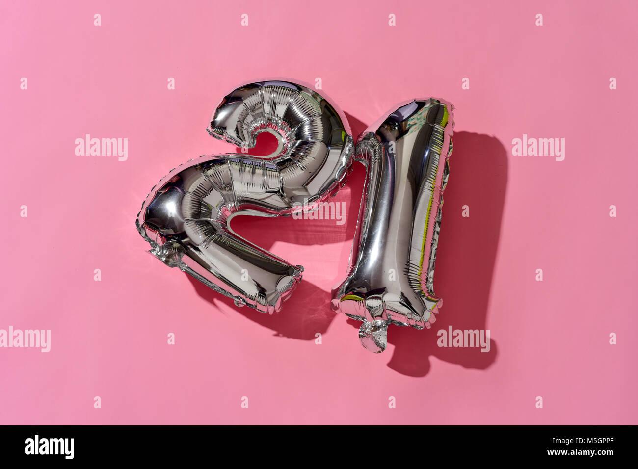 Certains ballons en forme de numéro argenté formant le numéro 21 contre un fond rose, avec un peu Photo Stock