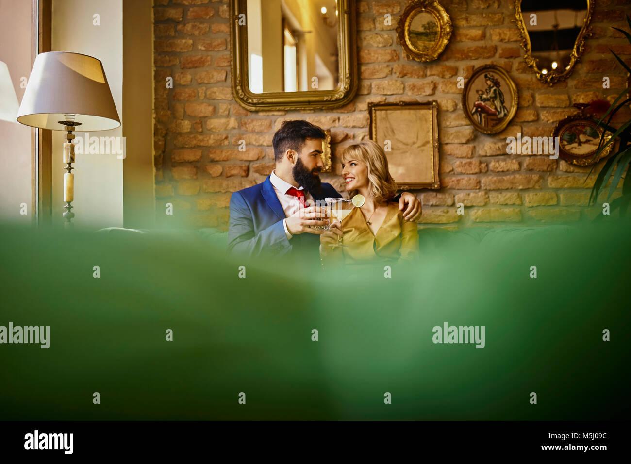 Couple élégant avec boissons sitting on couch embracing Photo Stock
