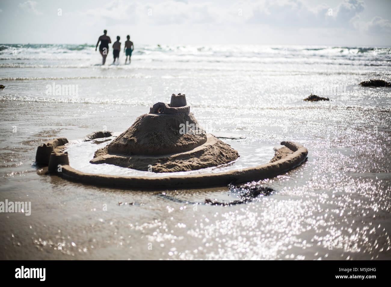 France, Normandie, Cotentin, Portbail, château de sable sur la plage et de la famille en arrière-plan Banque D'Images