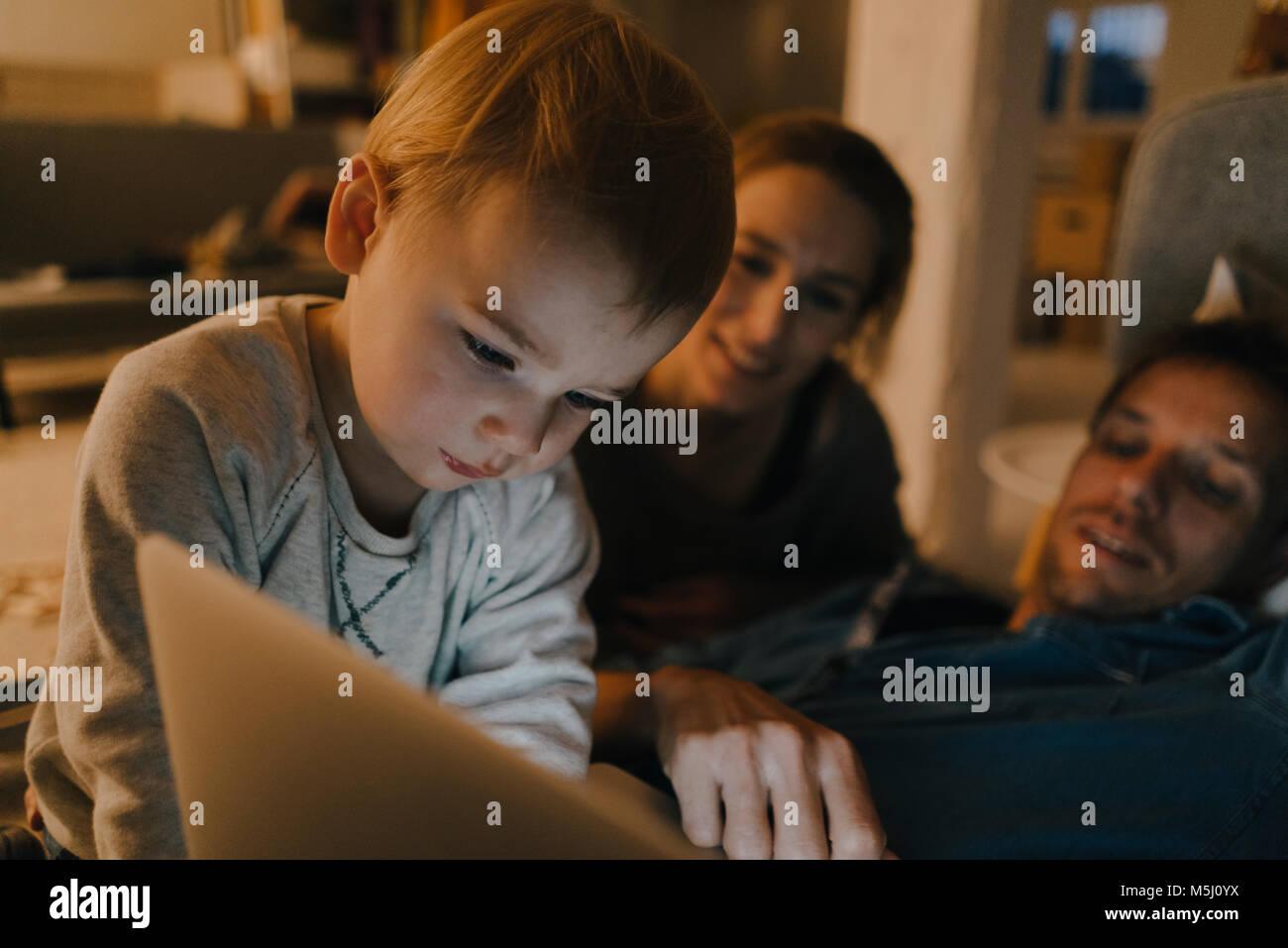 À l'aide de la famille de l'ordinateur portable sur le canapé dans le noir Photo Stock