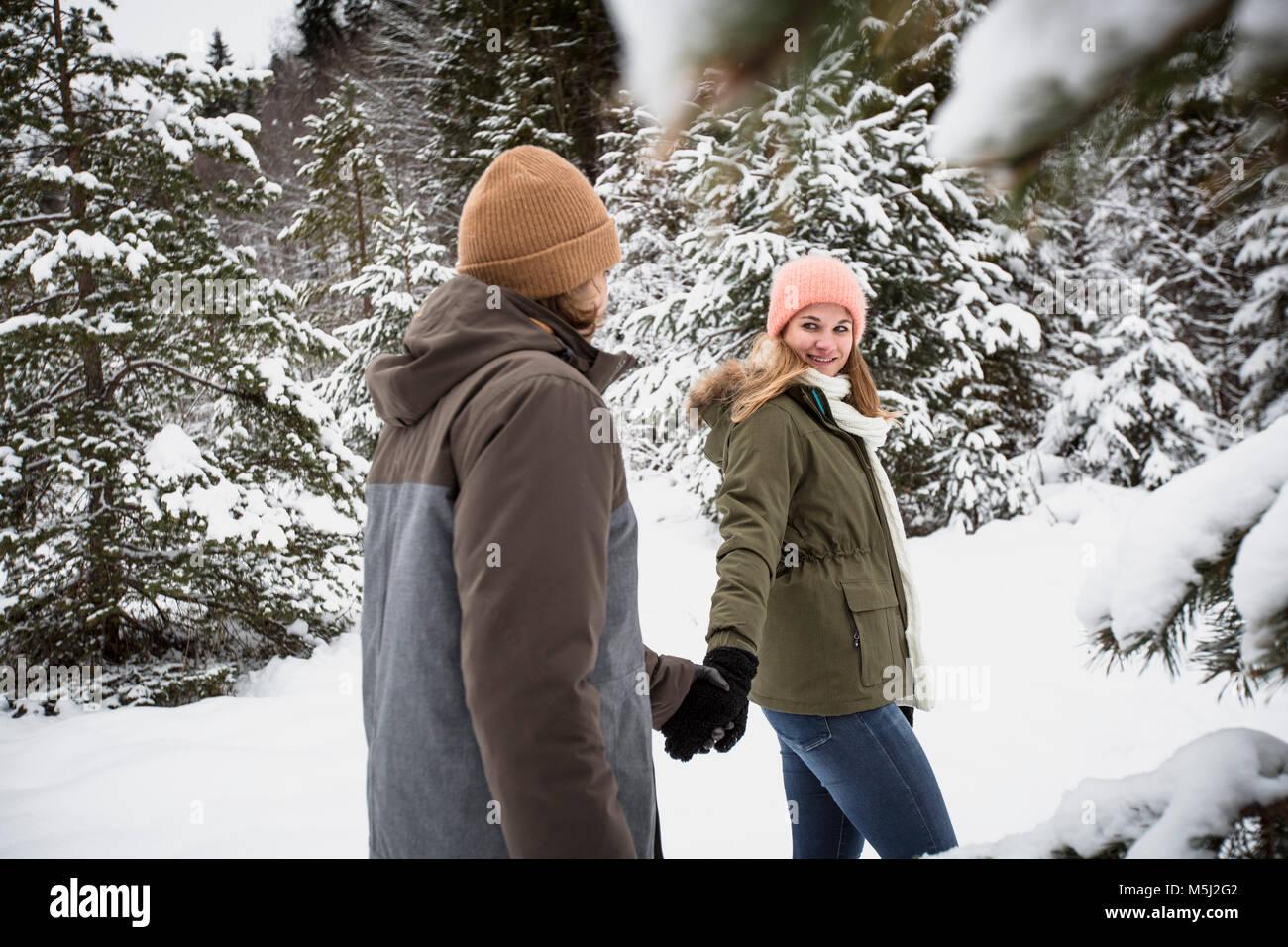 Couple en train de marcher dans la forêt d'hiver Photo Stock
