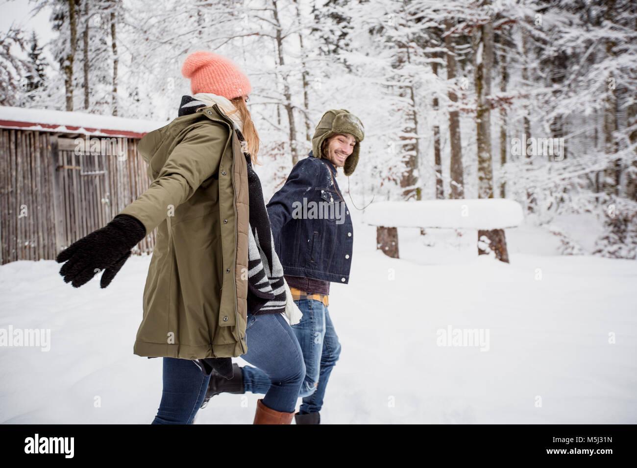 Couple heureux tournant à l'extérieur en hiver Photo Stock