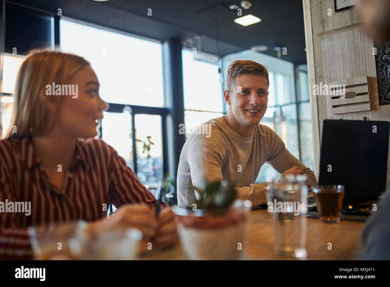 Smiling friends meeting in a cafe Photo Stock