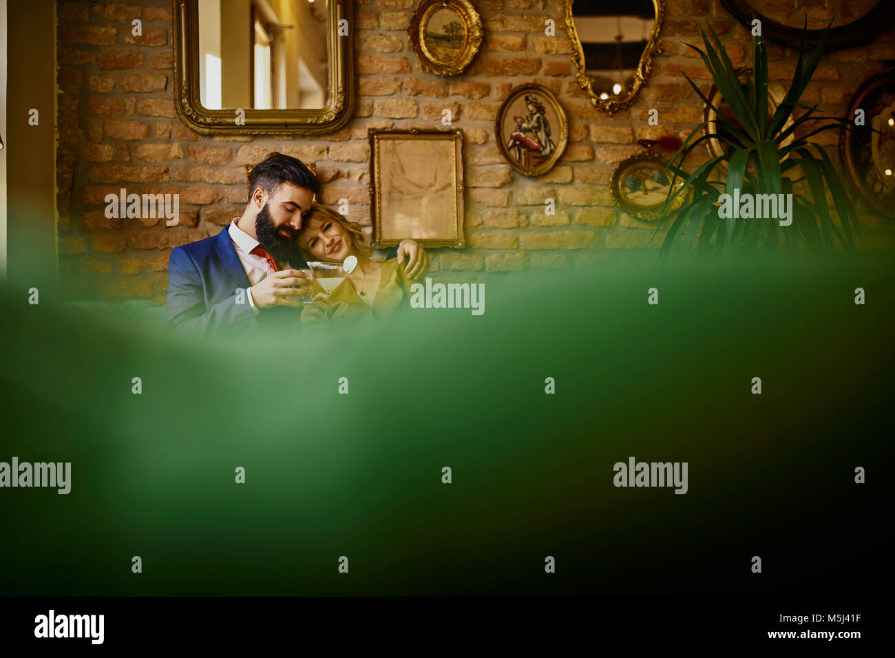 Couple élégant avec boissons sitting on couch hugging Photo Stock