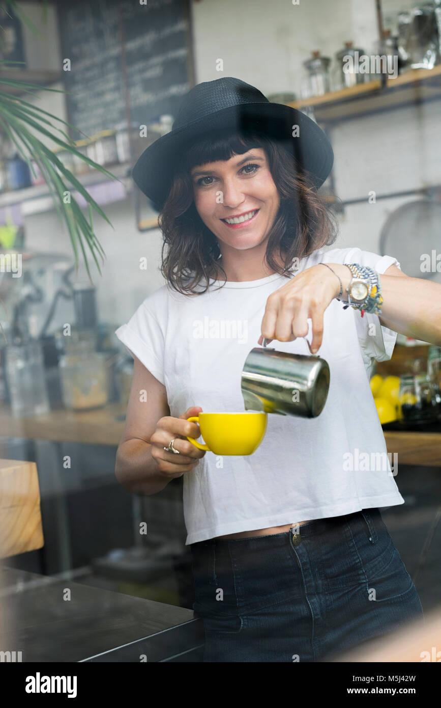 Portrait de femme au chapeau noir derrière le bar la préparation d'un café Photo Stock