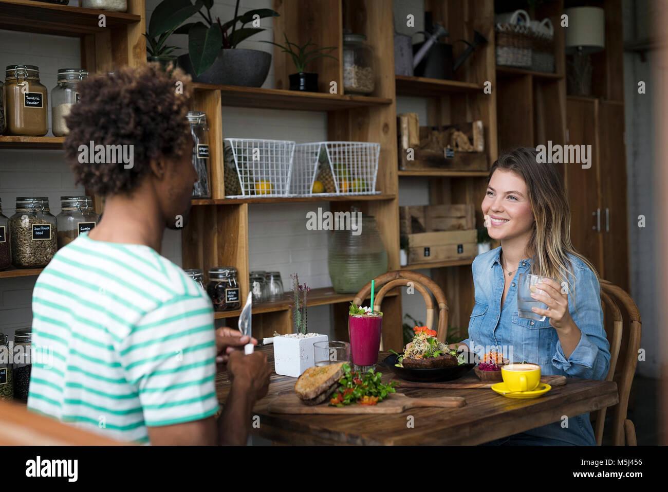 Smiling couple prendre un repas ensemble dans un restaurant confortable Banque D'Images