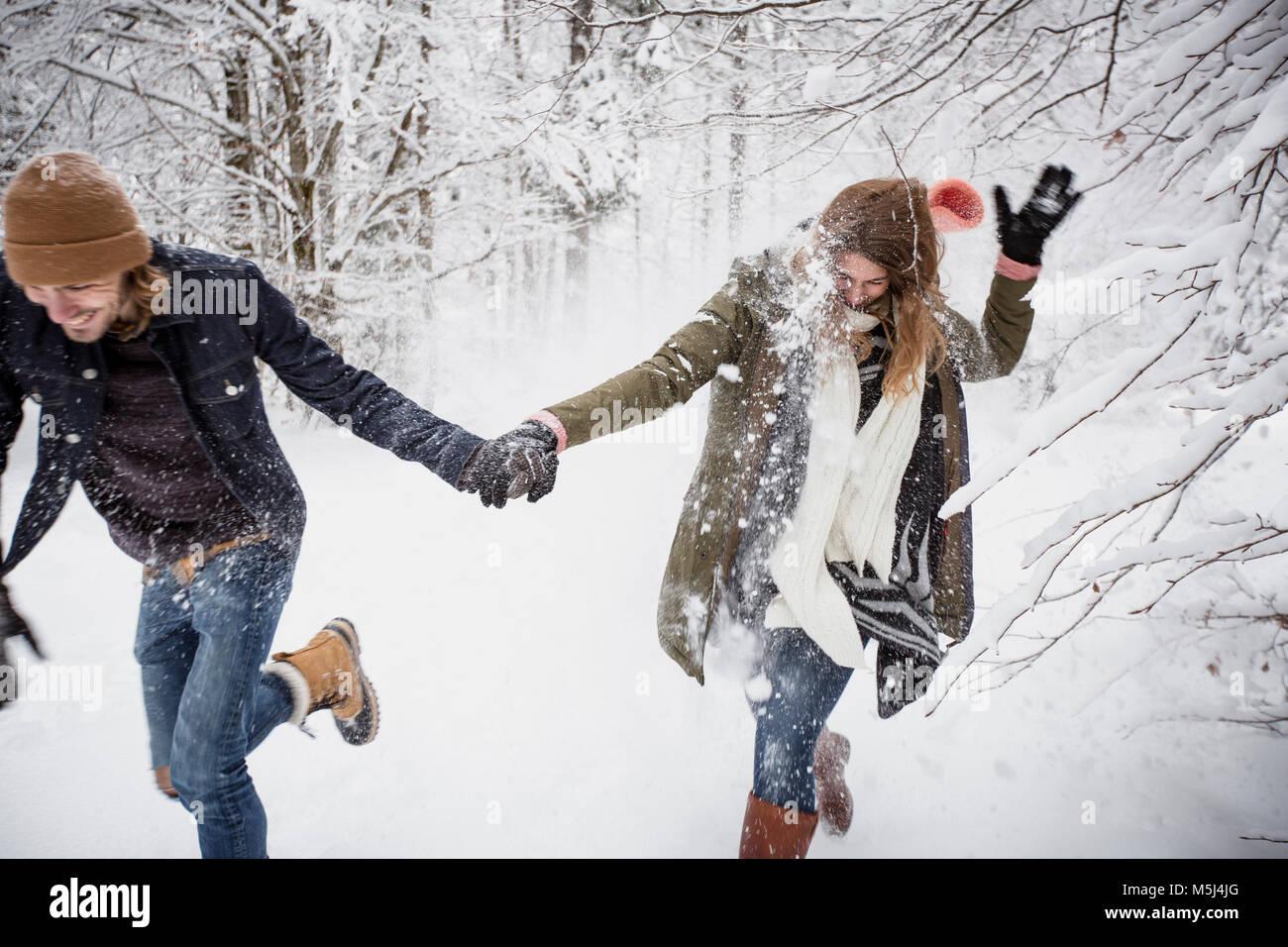 Heureux couple fonctionnant en forêt d'hiver Photo Stock