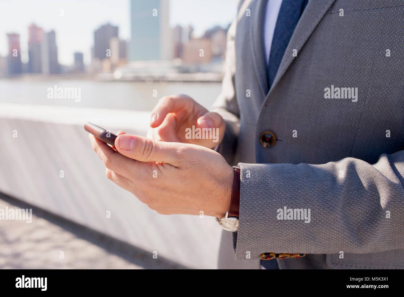 Businessman en utilisant son téléphone cellulaire sur un toit dans la ville Banque D'Images