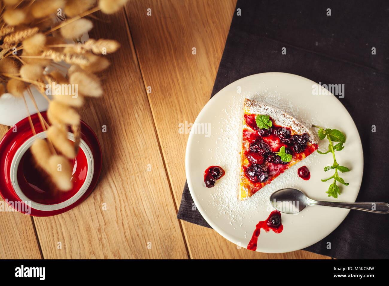 Belle italienne Cheesecake aux fruits rouges, de menthe et du sucre en poudre sur fond de bois, selective focus Photo Stock
