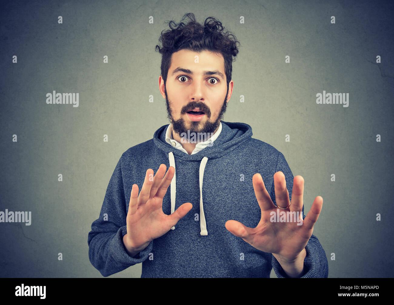 Jeune homme barbu looking at camera avec crainte et outstretching mains dans la panique. Photo Stock