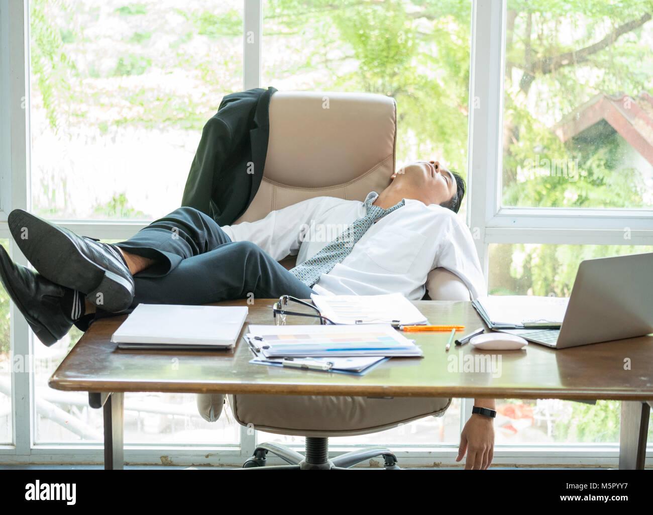 Homme d affaires fatigué dormir dans le bureau avec ses pieds sur