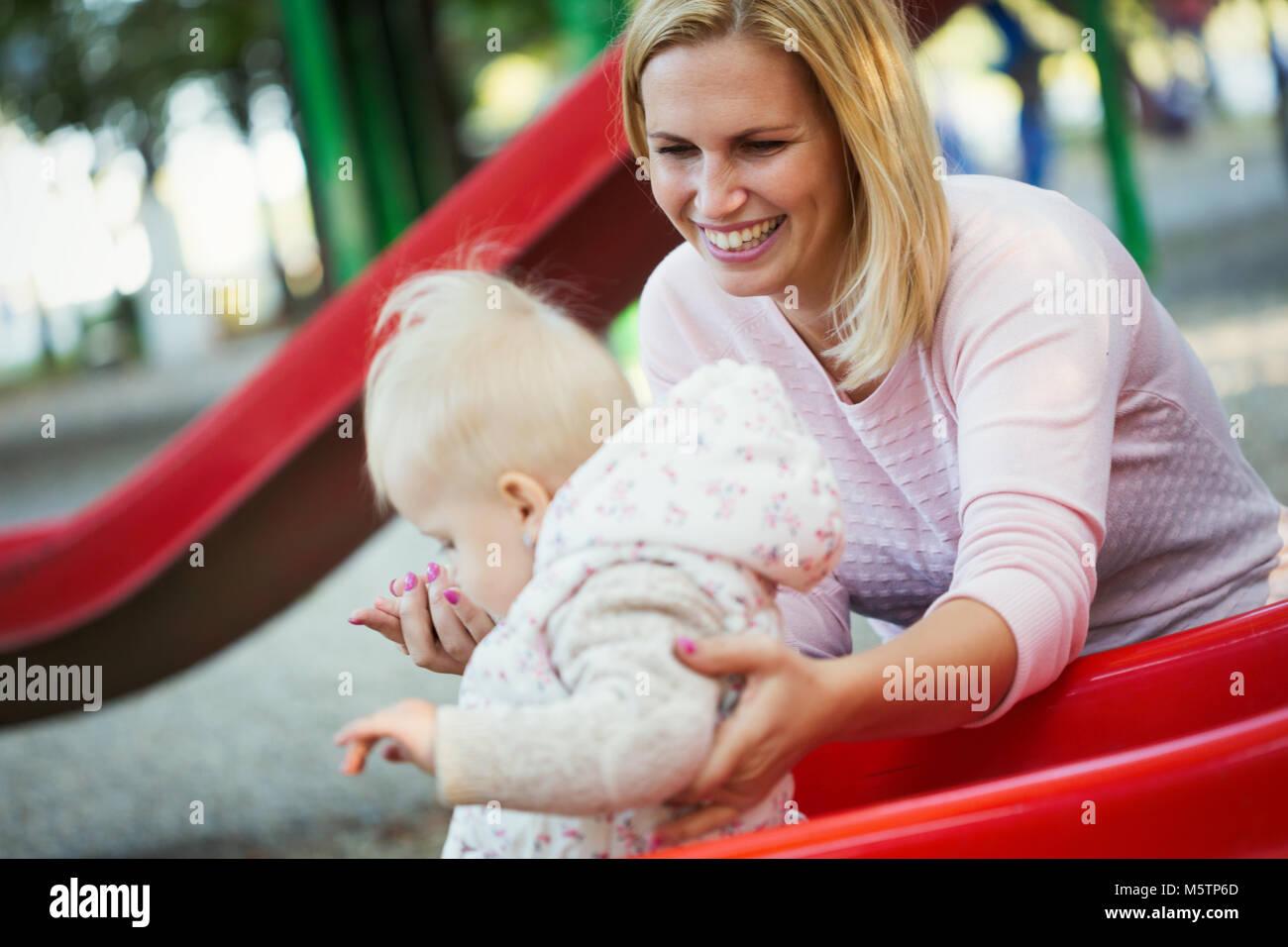 Petite fille et son beau jeune mère jouant sur l'aire de jeux Banque D'Images