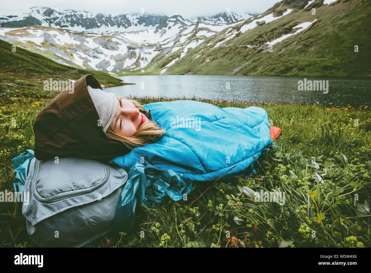 Woman relaxing in sac de couchage portant sur l'herbe profitant du paysage du lac et des montagnes de vie voyage Photo Stock