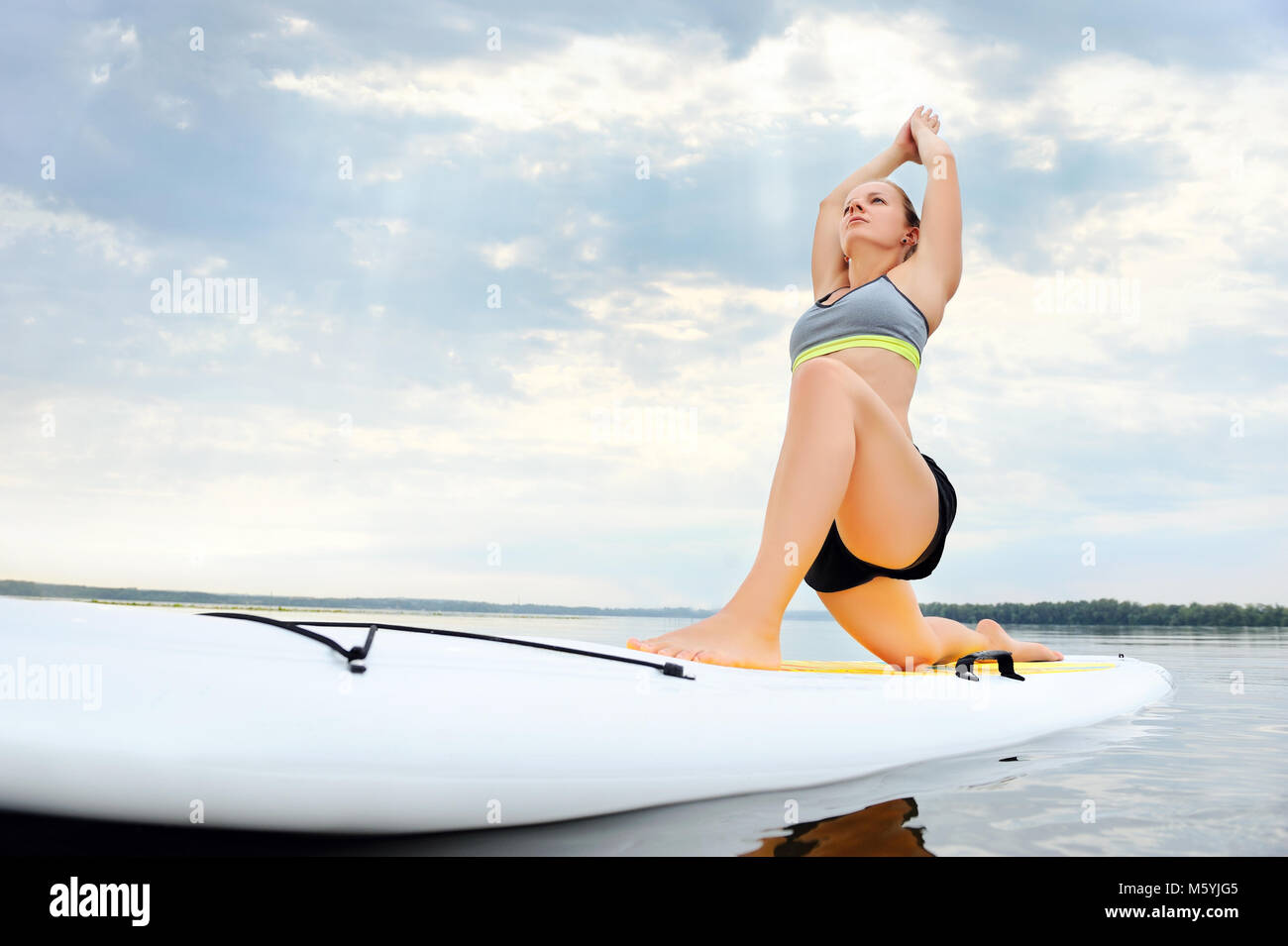 Vue grand angle de woman practicing yoga on conseil sup Photo Stock