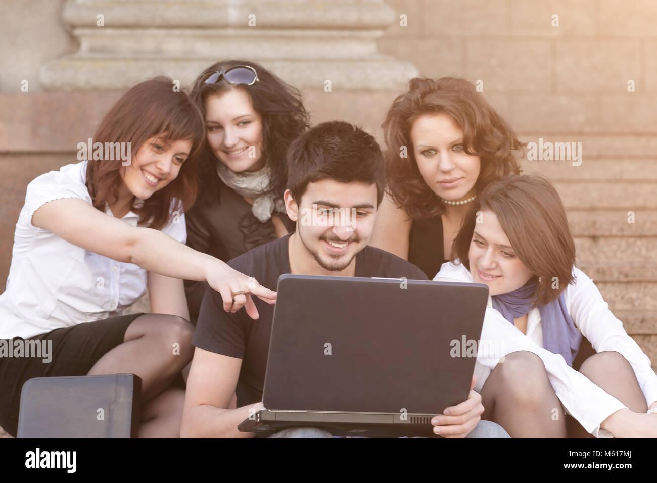 Groupe d'étudiants de discuter les informations avec l'ordinateur portable. Banque D'Images