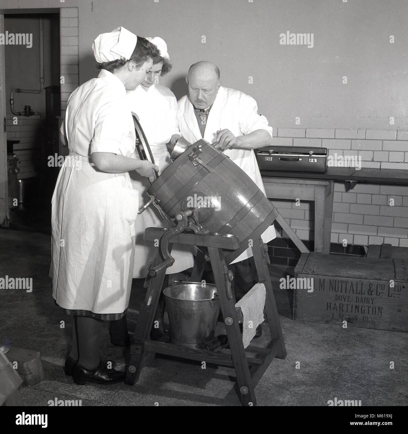 Années 1950, historiques, homme enseignant dans une usine laitière montrant deux femmes étudiant Photo Stock
