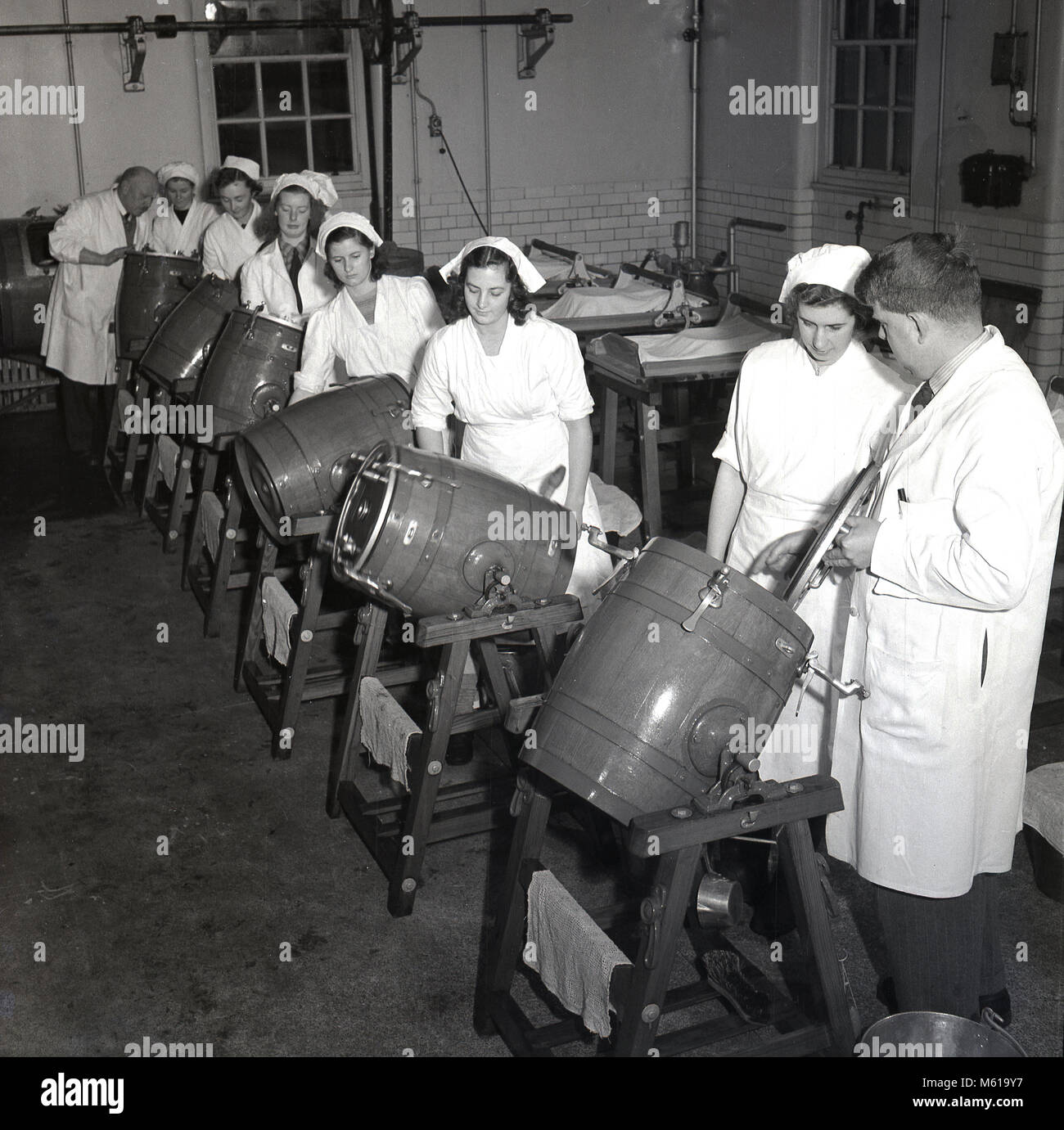 Années 1950, historiques, enseignant dans une laiterie montrant un groupe d'apprenants de sexe féminin Photo Stock