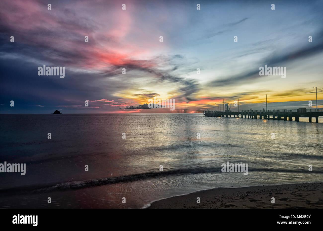 Fiery spectaculaire lever du soleil par la jetée de Palm Cove Beach, Cairns Plages du Nord, Extrême Nord Photo Stock