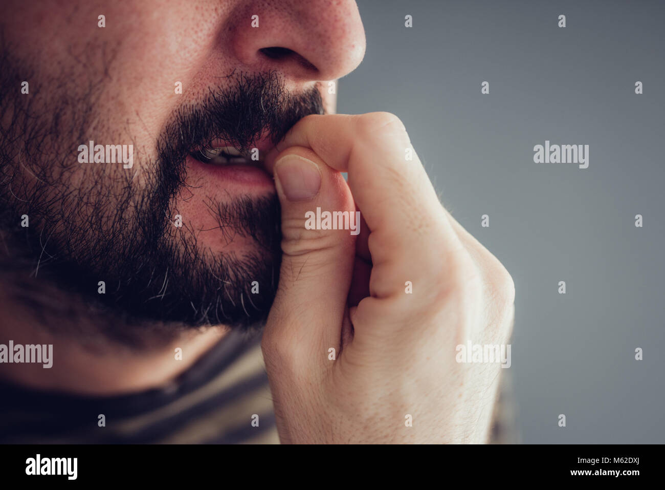 Close up of male biting fingernails nerveux Photo Stock