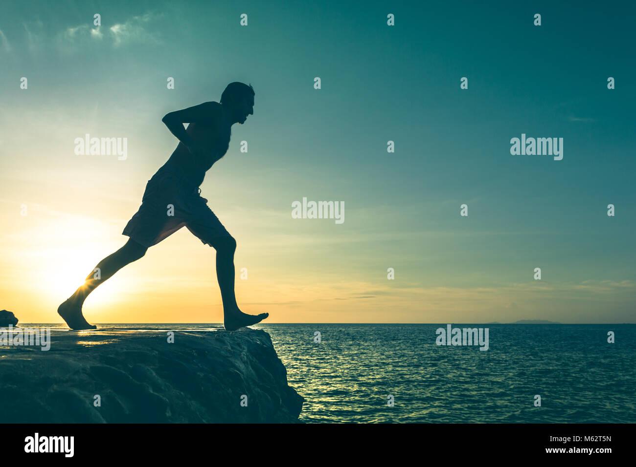 L'homme sur le bord d'une falaise sur le point de sauter dans la mer, sur le coucher du soleil dans l'île Photo Stock