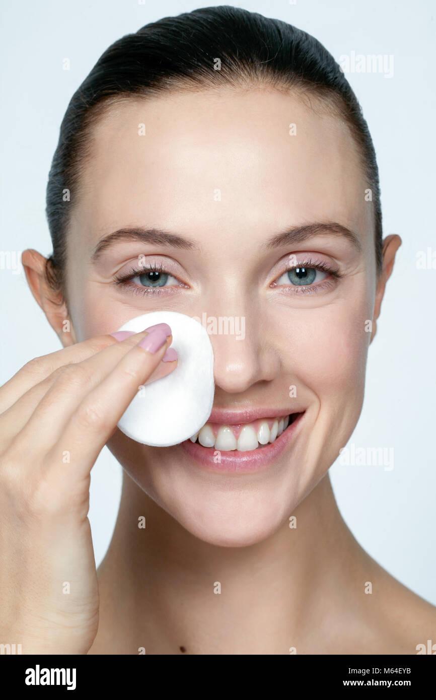 Nettoyage ethnique femme visage avec un coton Photo Stock