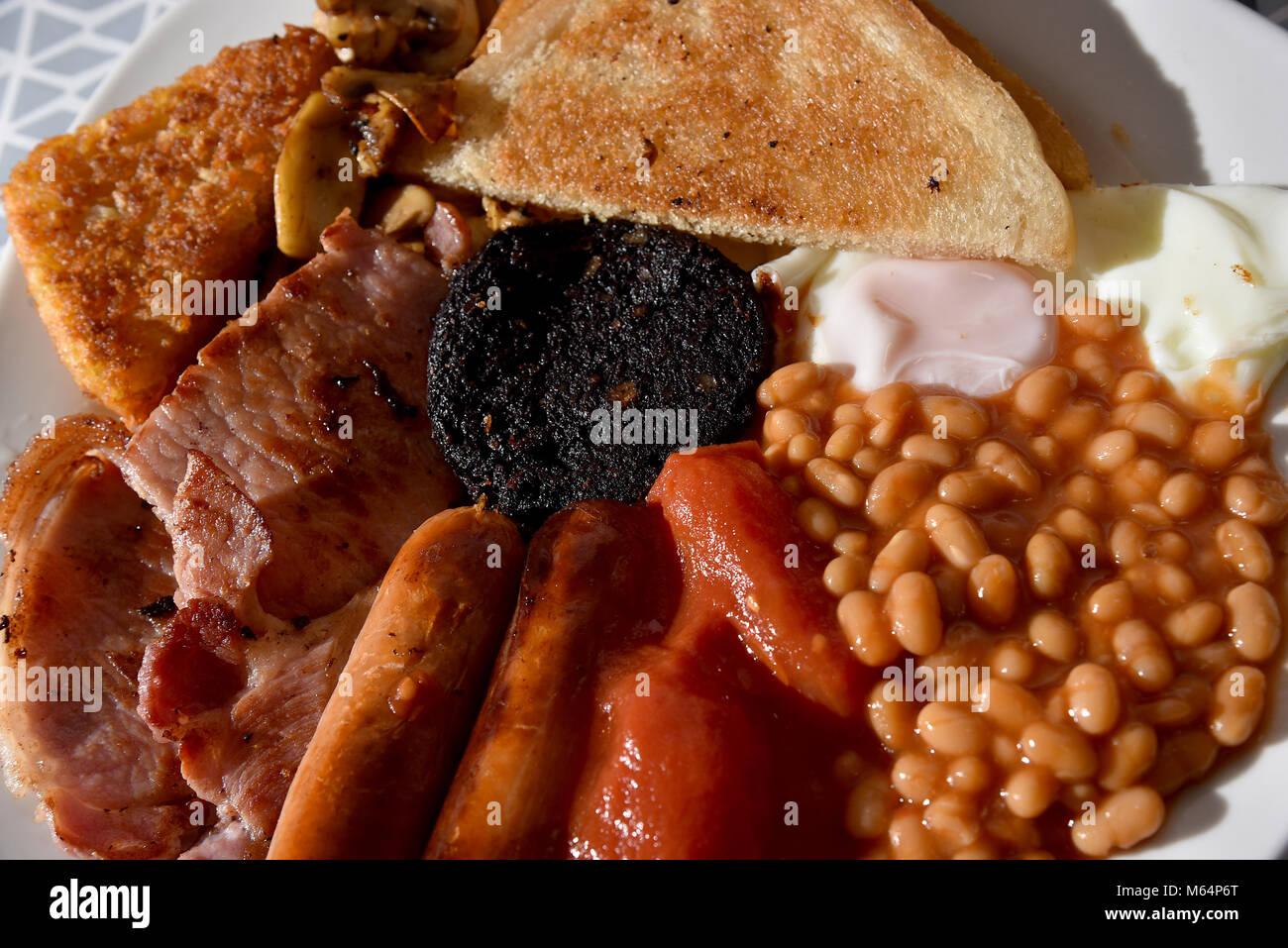 Petit-déjeuner anglais complet composé de bacon, saucisses, haricots blancs, pommes de terre rissolées, Photo Stock
