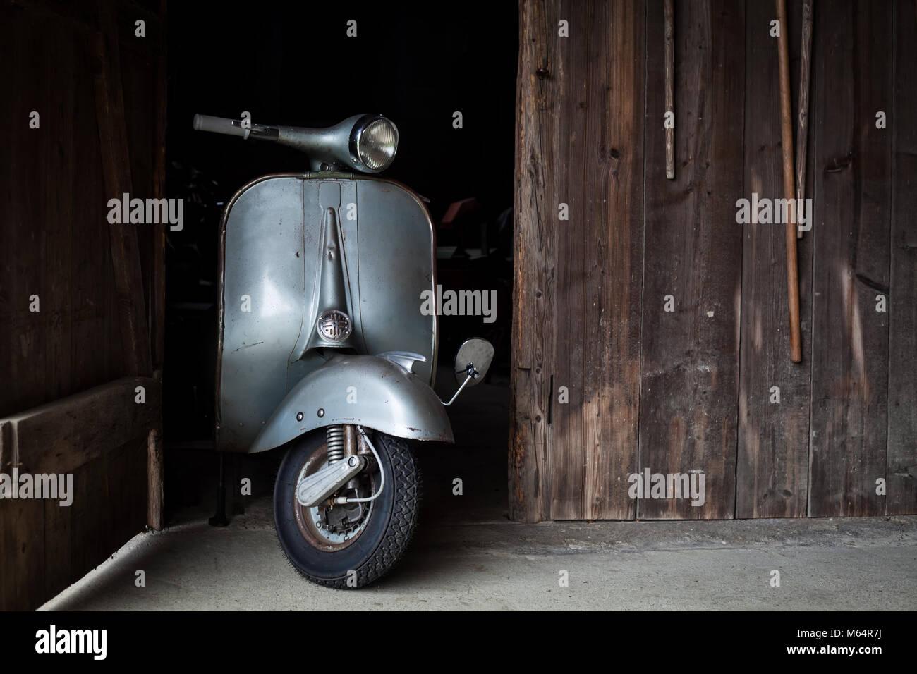 Trouver des vieux grange, Rusty de couleur bleu-gris scooter italien dans une cabane Banque D'Images