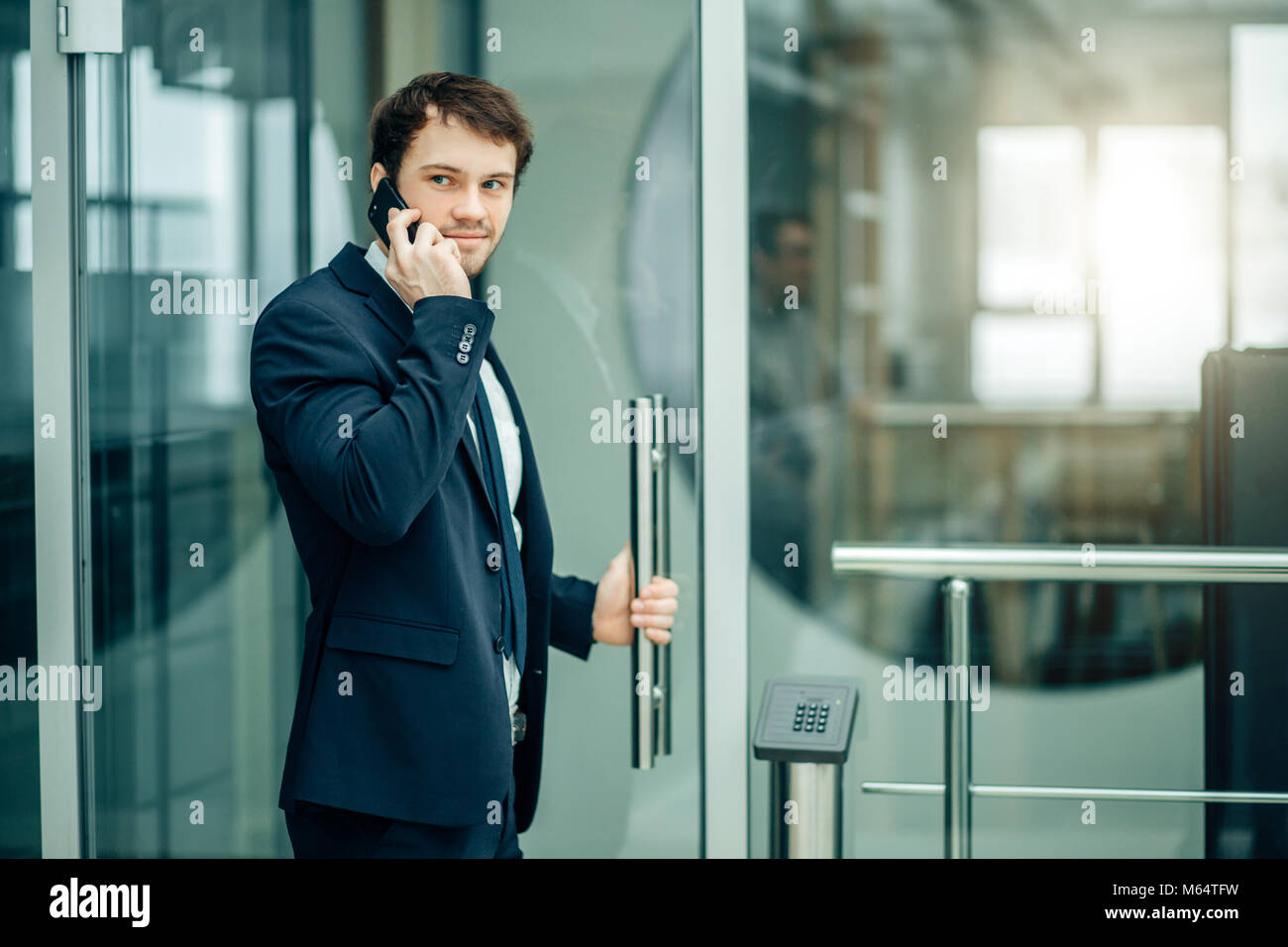 Business man walking while talking on mobile phone sur le chemin du travail Photo Stock