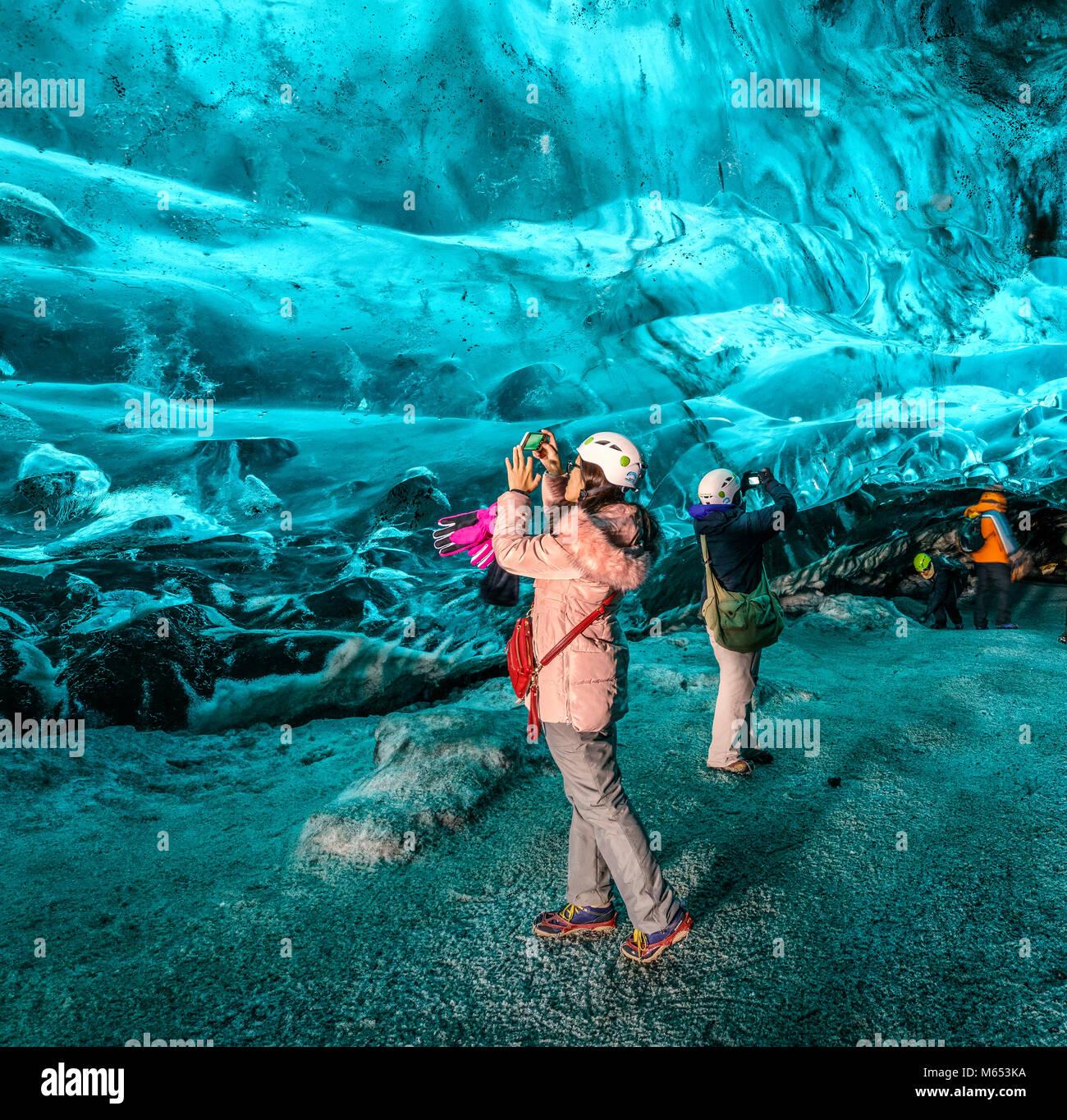 Les touristes dans la grotte de cristal, Glacier Breidamerkurjokull, Islande. La glace bleue émeraude et le Photo Stock