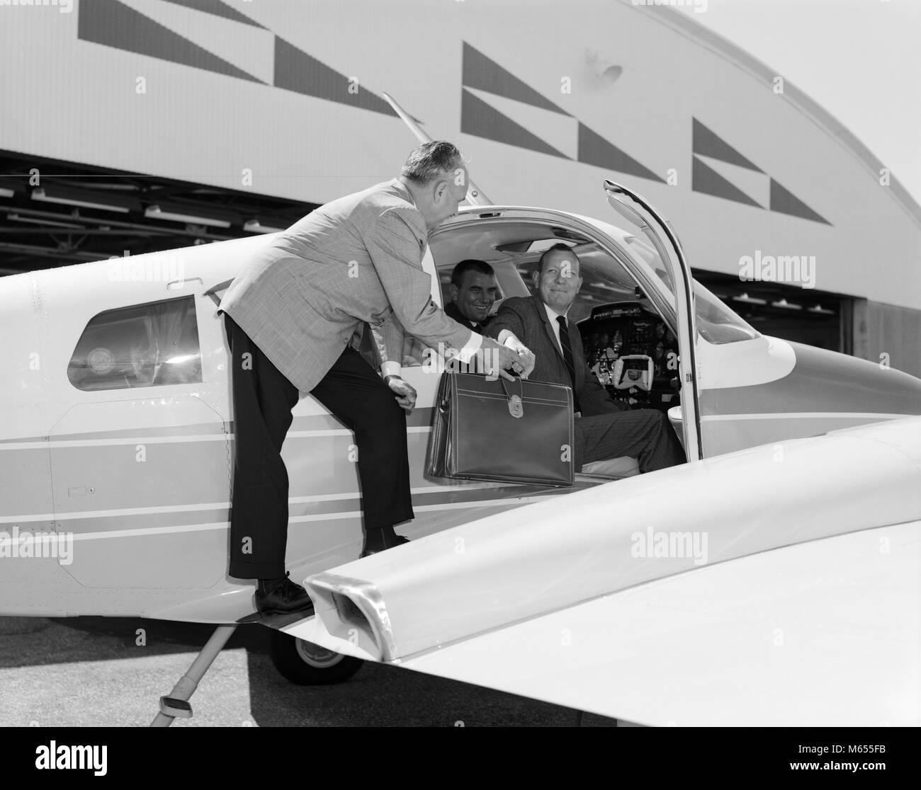 1960 SMILING BUSINESSMEN EN Cessna 310G AVION BIMOTEUR REMISE HOMME Serviette en cuir à PASSAGER - UN5808 KRU001 Photo Stock