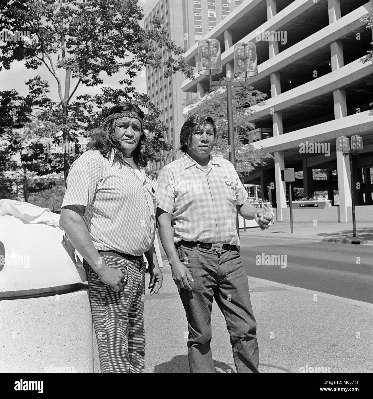 1970 LES DEUX HOMMES INDIENS CHIPPEWA FRÈRES LOOKING AT CAMERA STANDING BY CITY PARK MINNEAPOLIS MN USA - i6152 Photo Stock