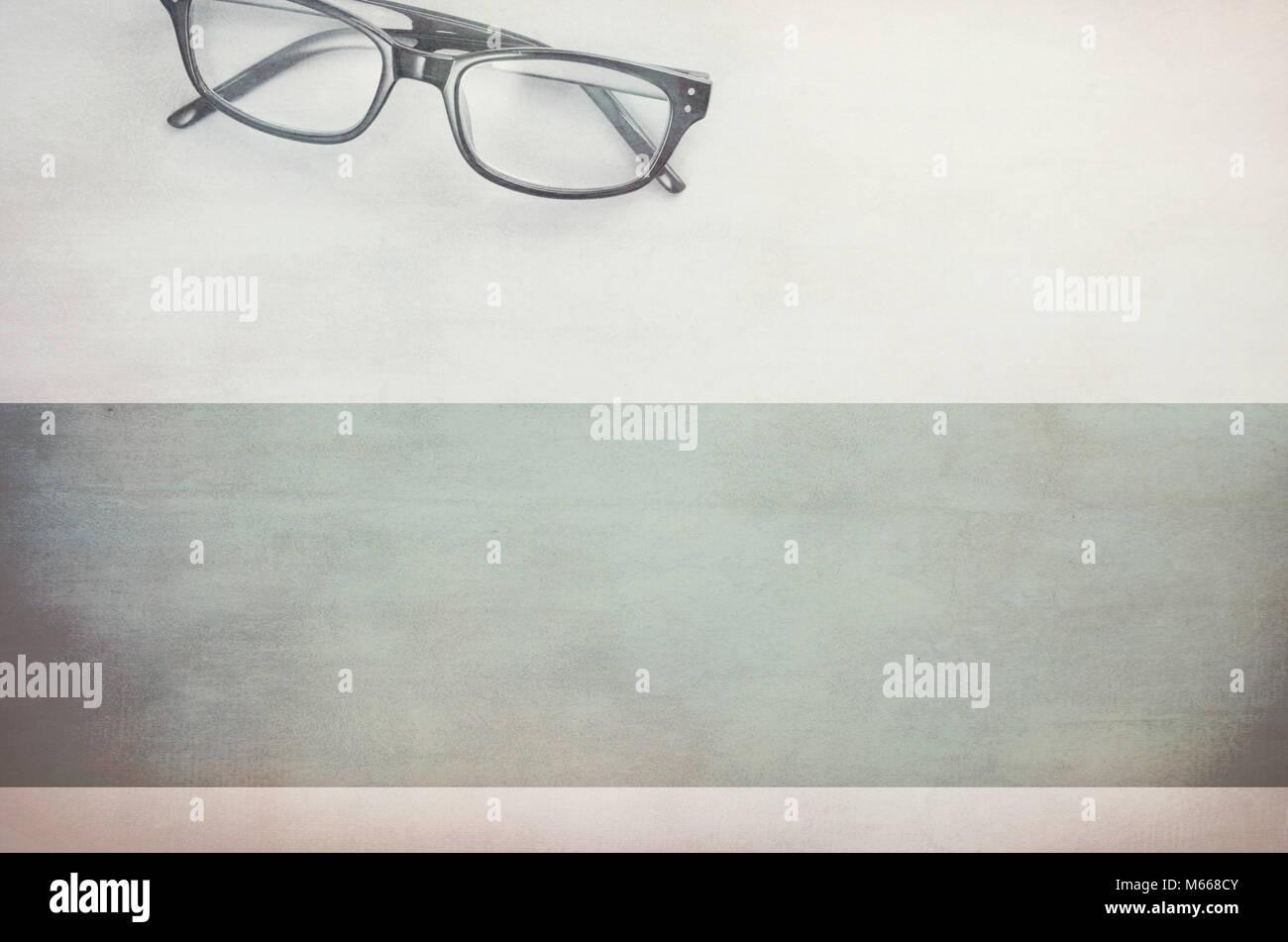 Paire de lunettes encadrées sur une surface à texture légère - directement au-dessus Photo Stock